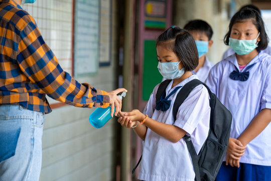 Teacher and elementary children with face mask are disinfecting