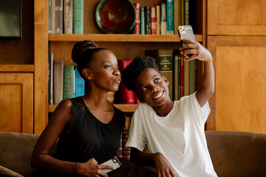 Black mom and smiling son taking selfie in front of bookcase