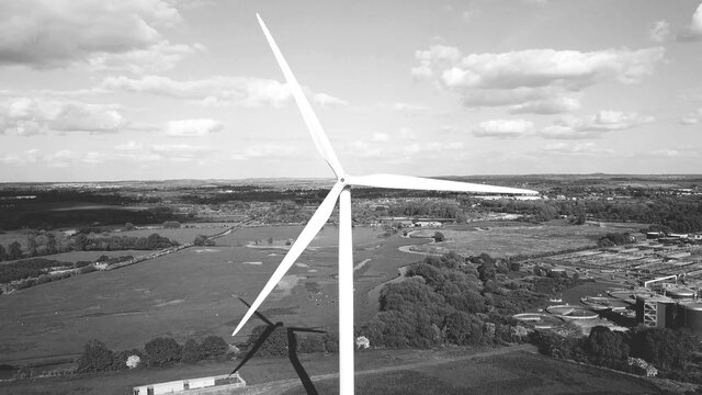 Wind turbine, industrial area agricultural fields in background, clean energy production, black and white aerial view.