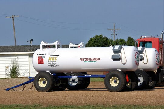 Anhydrous Ammonia Tank in a farm yard with a building and tree's north of Hutchinson Kansas USA.
