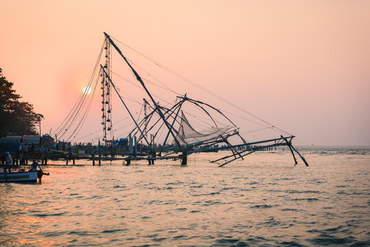 Traditional Chinese fishing nets called Cheena vala, a typical view and Unesco World heritage site at sunset, in Kochi coastal shore, in India