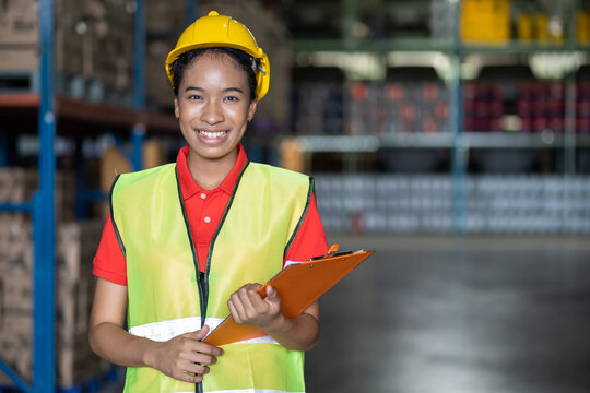 Portrait of African American smiling female warehouse worker with clipboard working and checking products or parcel goods on shelf pallet in industrial storage warehouse