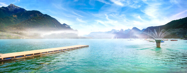Sankt Gilgen on Wolfgangsee (lake Wolfgang). View to the lake with jetty, fountain and mountains covered with fog