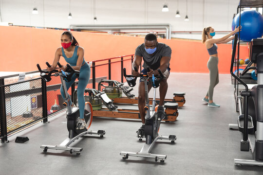 Fit african american man and fit caucasian woman wearing face masks exercising on stationary bike in