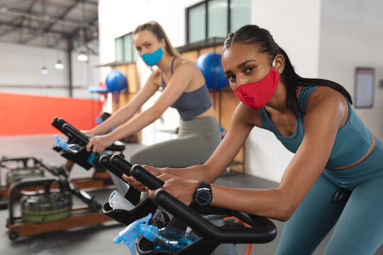 Portrait of two fit caucasian woman wearing face masks exercising on stationary bike in the gym