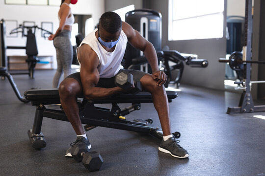 Fit african american man wearing face mask performing exercise with dumbbell in the gym