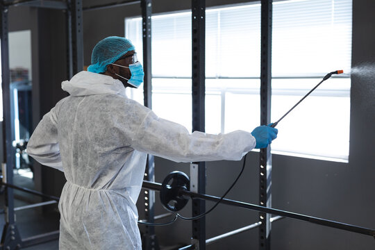 Male worker wearing protective clothes and face masks cleaning the gym using disinfectant