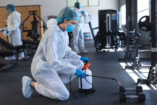 Female worker wearing protective clothes and face masks cleaning the gym using disinfectant