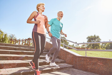 Energize your morning. Full length shot of active mature family couple in sportswear running together in the park on a sunny morning. Joyful senior couple working out outdoors Wall mural