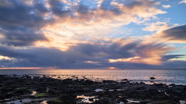 Sunrise and dawn sky over the North Sea off Brora in Sutherland with a lobster fishing boat on the ocean