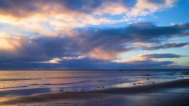Sunrise and dawn sky over the North Sea off Brora beach in Sutherland with a lobster boat sailing from Brora harbour