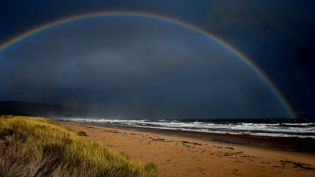 Heavy rain sweeping across a stormy sea and sandy beach with a full rainbow in a dark sky