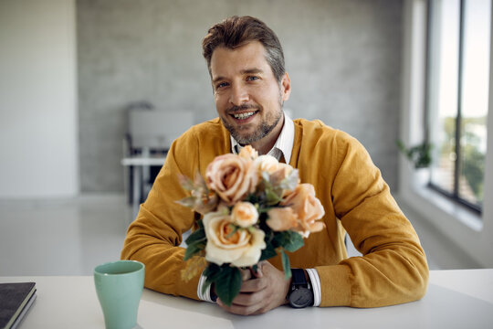 Happy businessman holing a bouquet of roses and looking at the camera.