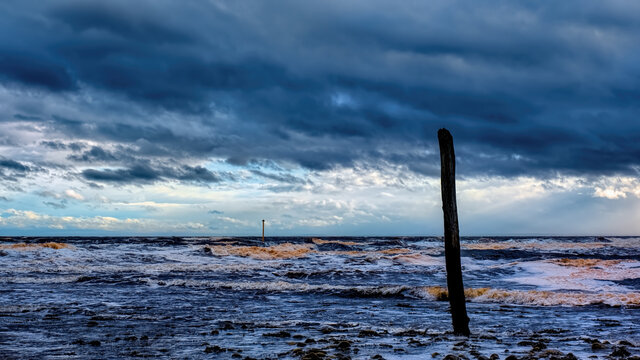 Stormy seas and heavy skies at the River Brora estuary with markers for the harbour