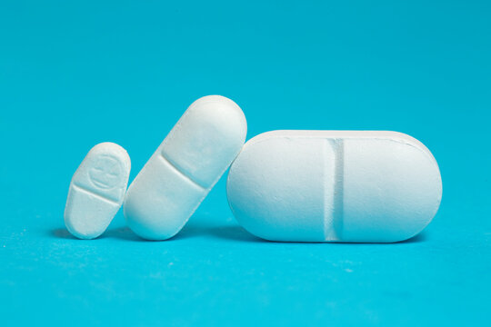 Three white  pills of different sizes on blue, dosage