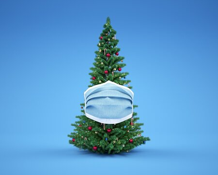 Christmas tree protected with a surgical mask. Blue background.