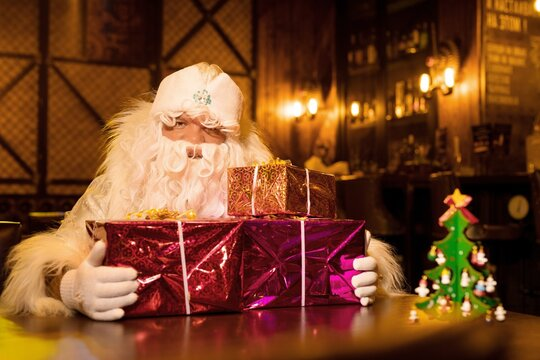 Santa Claus with pile of gifts in bar
