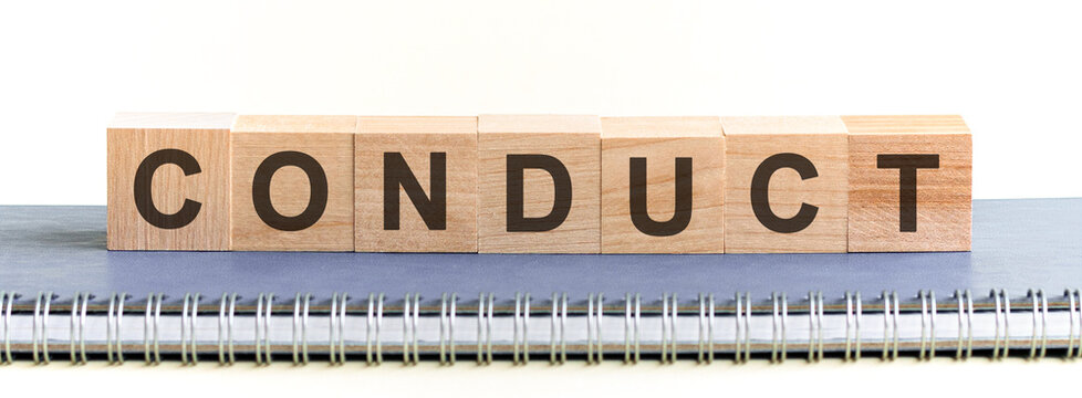 CONDUCT - a word made of wooden blocks with black letters, a row of blocks is located on a grey notepad