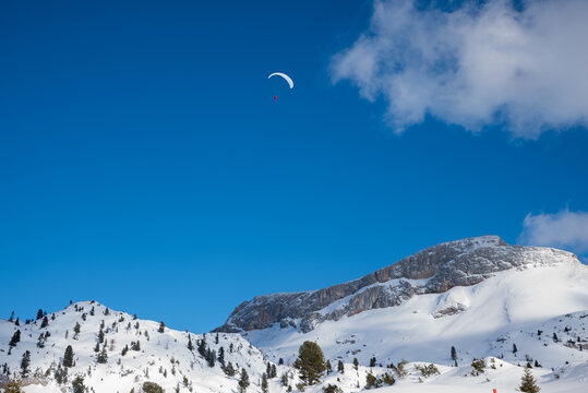 paraglider above Rofan mountains, winter landscape with blue sky and clouds