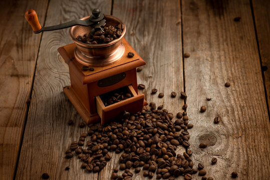 Coffee grinder with coffee beans over wood
