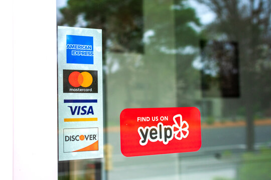 MasterCard, VISA, American Express, Discover payment options advertised on a restaurant door. A red sticker decal promotes Yelp crowd-sourced reviews service - San Francisco, California, USA - 2020
