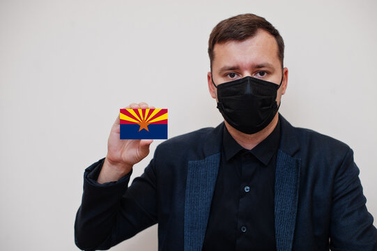 Man wear black formal and protect face mask, hold Arizona flag card isolated on white background. USA coronavirus Covid country concept.