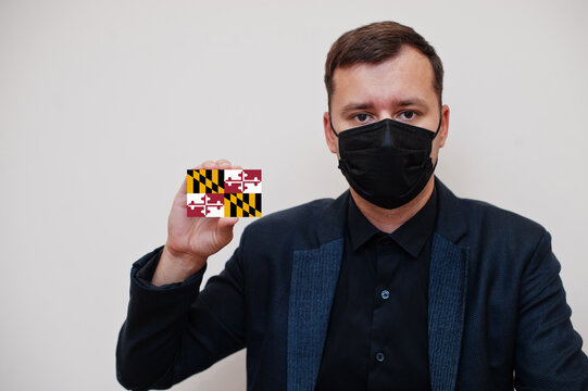 Man wear black formal and protect face mask, hold Maryland flag card isolated on white background. USA coronavirus Covid country concept.