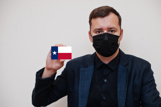 Man wear black formal and protect face mask, hold Texas flag card isolated on white background. USA coronavirus Covid country concept.