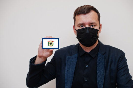Man wear black formal and protect face mask, hold West Virginia flag card isolated on white background. USA coronavirus Covid country concept.