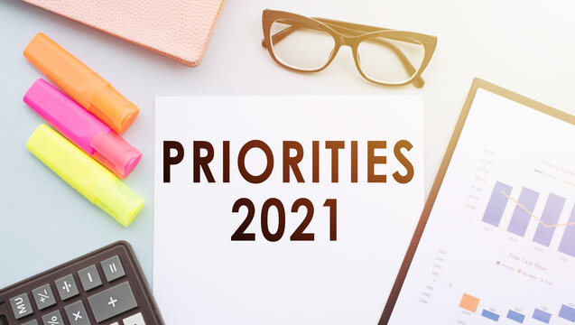 A sheet of white paper with the text Priorities 2021 on a white table, next to a calculator and office supplies.