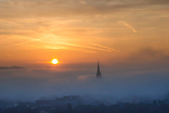 Cityscape of Graz with Church of the Sacred Heart of Jesus and historic buildings, in Graz, Styria region, Austria, at sunrise. Beautiful foggy morning over the city of Graz, in autumn