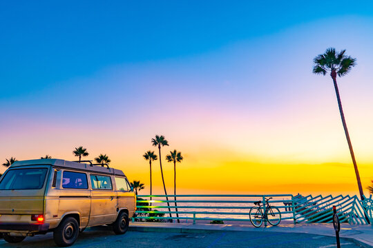 Scenic beach coast sunset view with tall California palm trees near the ocean and vintage van parked behind rail in street parking lot. Stunning sky colors at dusk.
