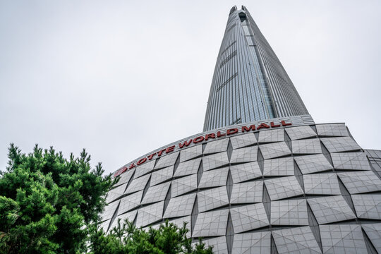 Lotte tower mall sign and Lotte World Tower a supertall skyscraper in Seoul South Korea