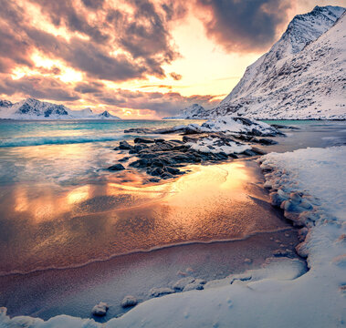 Colorful winter sunset on Lofoten Islands, Norway, Europe. Breathtaking morning scene of popular tourist destination - Skagsanden beach, Flakstadoya island. Untouched Winter Landscape.
