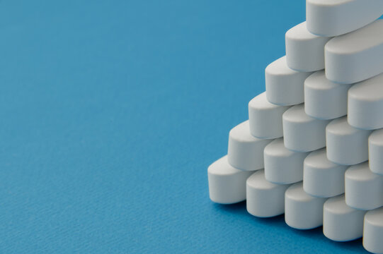 many pharmacological white tablets pills on blue background with copy space