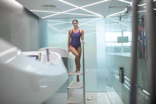 Dark-haired female in purple swimming suit getting into hydromassage bathtub