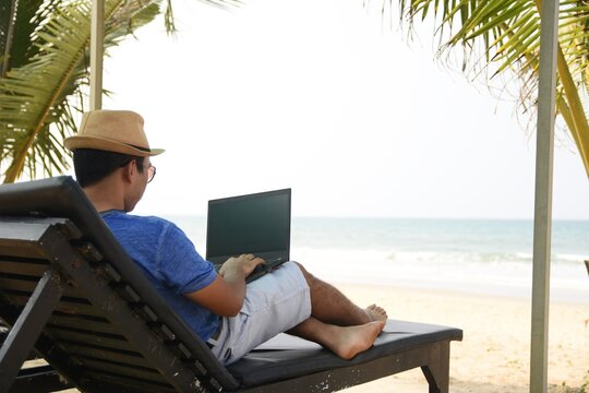 A man using his laptop and working from sea beach, during this pandemic where work from home is part of life , now people can work from anywhere and at the same time have a feel of vacation.