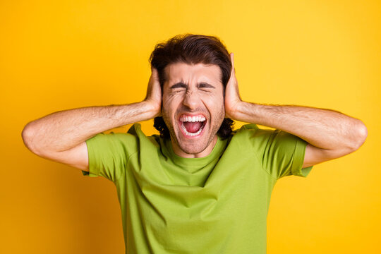 Photo of annoyed mad man palms cover ears open mouth closed eyes wear green t-shirt isolated yellow color background