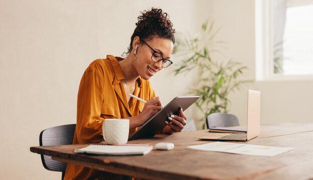 Female designer at home sketching on a digital tablet