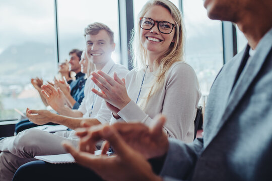 Group of business people clapping hands at seminar