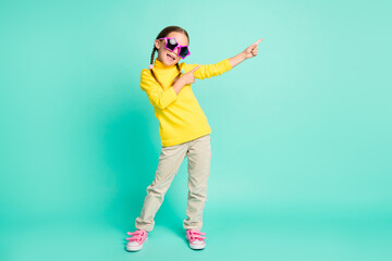 Full length photo of cheerful brown haired girl point empty space wear white pants yellow turtleneck isolated on teal color background Wall mural