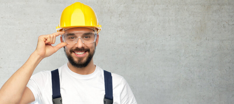 profession, construction and building concept - happy smiling male worker or builder in yellow helmet and overall over grey concrete background
