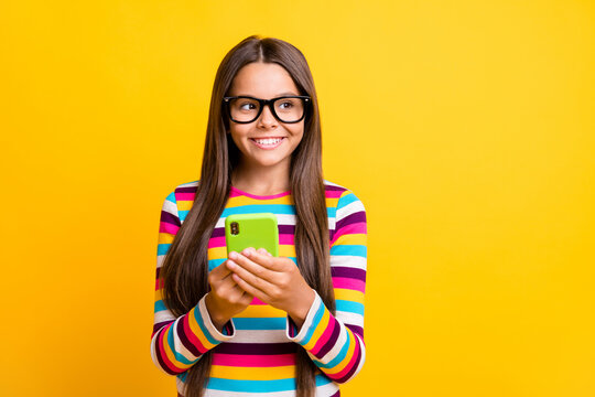 Photo portrait of curious girl keeping cellphone smiling wearing glasses looking at blank space isolated on bright yellow color background