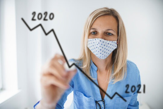 Business woman with face mask drawing falling graph for 2021
