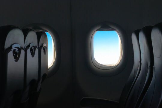 Beautiful low key photograph of cabin interior of passenger airplane, with amazing blue tint of sky from window. It is flying vacant and empty due to low demand of air travel during Covid-19 pandemic.