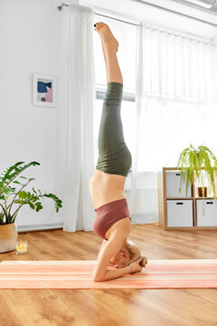 pregnancy, sport and people concept - happy pregnant woman doing yoga headstand at home