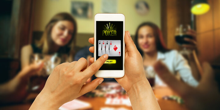 Online gambling, casino concept. Hand holding device with lottery, casino cover. Celebrating happy people on the background. Poker, bookmaking, gaming, modern technologies, business and finance.