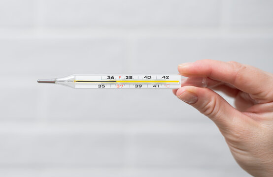 A medical thermometer in the woman's hand shows the patient's normal body temperature - 36.6 degrees. The disease is asymptomatic or the patient is recovering, or he is healthy. Light background.