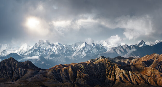 Panoramic view of the scenic landscape of snowy mountains and dramatic clouds