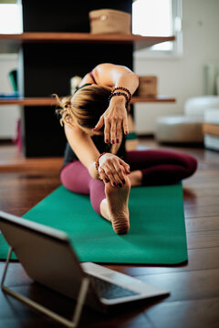 Middle-aged flexible woman sitting at home in head to knee yoga posture and following instruction over laptop.